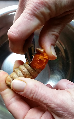 Peel fresh turmeric into a square of cheesecloth with a spoon.